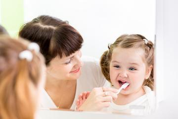 Mother helping young girl brush her teeth l Children's Dentistry Burien WA