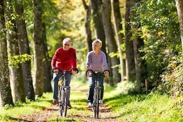 Older couple riding bikes in forest l Dental implants burien WA