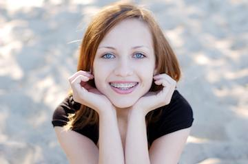Young woman with braces smiling l Orthodontics Burien WA